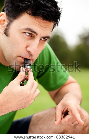 Male fitness coach blowing whistle