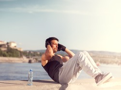 Male fitness model in urban area on wall doing sit ups and crunches exercising abdominal muscles