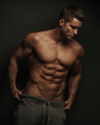Male fitness model standing on black background with holding his pants