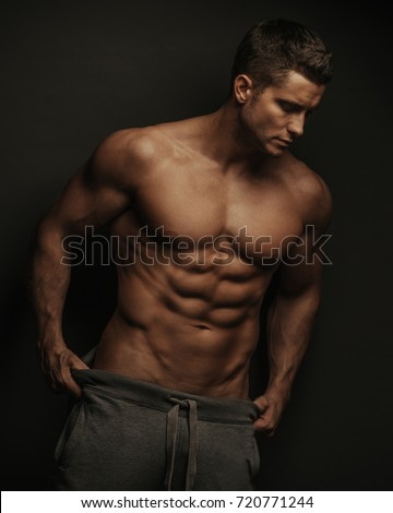 Male fitness model standing on black background with holding his pants Stock photo ©