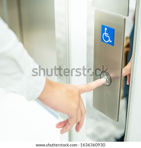 Male forefinger pressing on up button of elevator for blind or disability people (disabled lift). Handicap lift for hospital or medical center.
