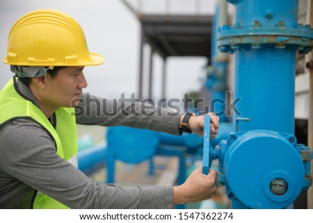 Male foreman wearing yellow safety helmet turning big valve