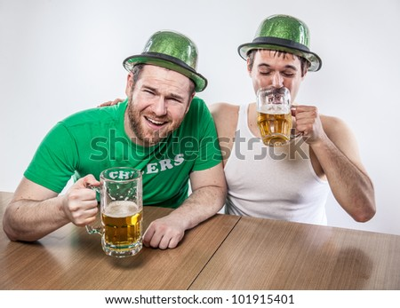 Male friends drinking on Saint Patrick's Day from large mugs of lager in green hats, wife beater, shirt, at favorite tavern having a good time