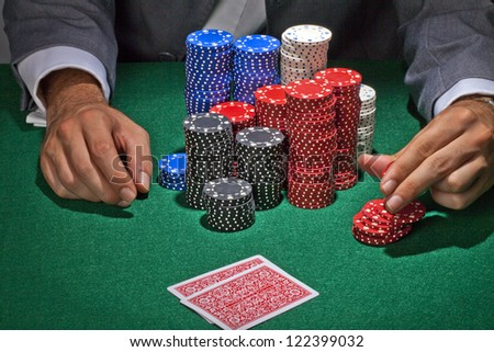 Male gambler playing in the casino on the green table