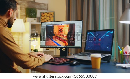 Male game developer typing on keyboard while developing a new level of the game. Foto stock ©