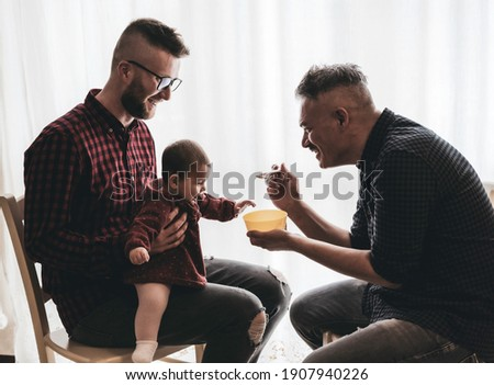 Male gay couple with adopted baby girl at home - Two handsome dads feed the baby girl on kitchen - Lgbt family at home, Diversity concept - Vintage filter Stockfoto ©