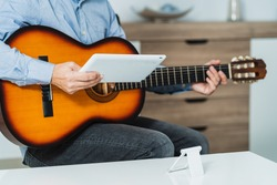 Male giving a guitar class online with the tablet, he is reviewing the lesson