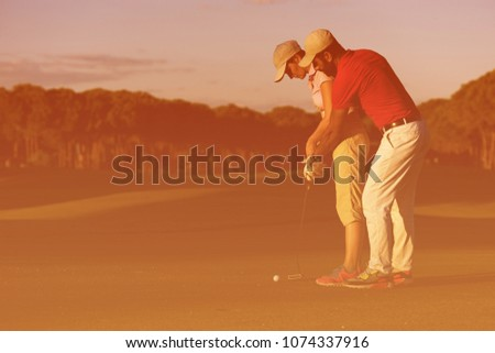 male golf instructor teaching female golf player, personal trainer giving lesson on golf course #1074337916