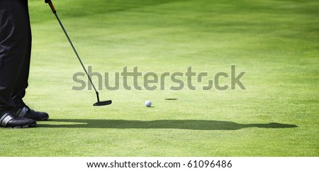 Male golf player in black with shadow putting on green with ball rolling towards hole, with plenty of copy-space.