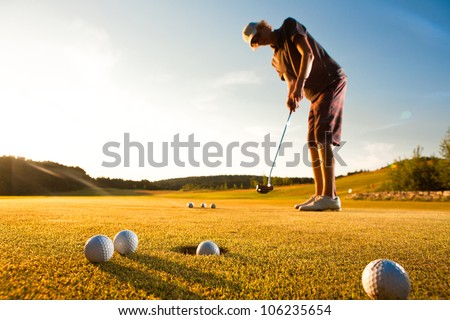 Male golf player practicing a par during beautiful evening sunshine light