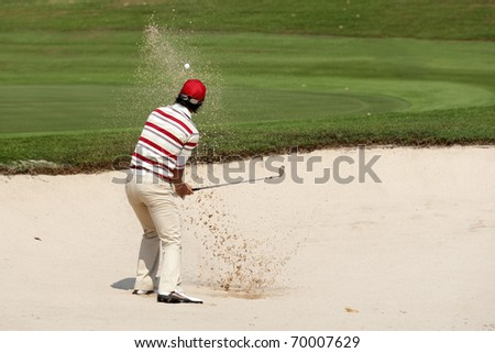 Male golf player put golf ball in sand,