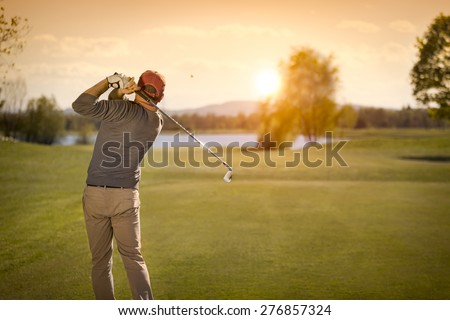 Male golf player swinging club at beautiful sunset in background, with empty copyspace.