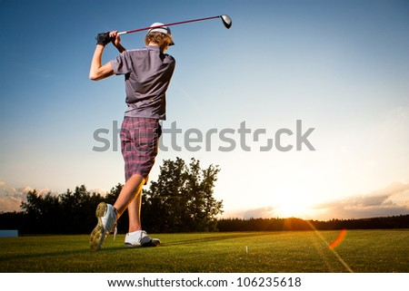 Male golf player teeing off golf ball from tee box to beautiful sunset