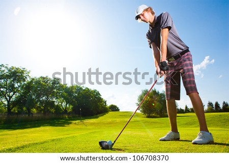 Male golf player teeing off golf ball from tee box with clean blue sky background