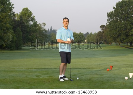 Male golfer casually standing on green holding golf club. Horizontal framed shot. - stock photo