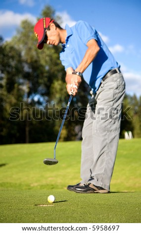 male golfer in putting green about to put the ball in the hole