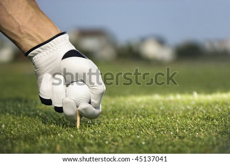 Male golfer places a golf ball and tee in the ground. Horizontal shot.