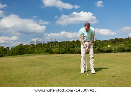 male golfer putting on green against blue sky