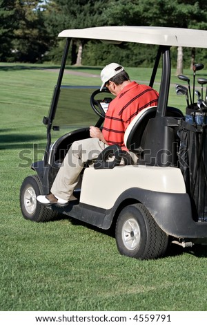 Male golfer sits in cart records his score on score card.