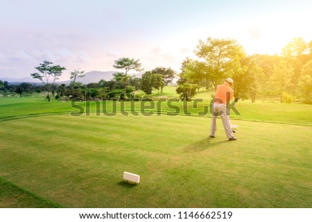 Male golfer teeing off golf ball from tee box on the Course to beautiful sunset.