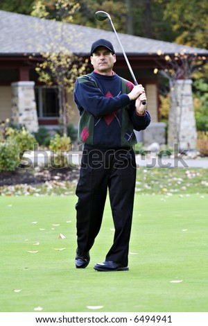 Male golfer tees of  in front of club house on an autumn day.