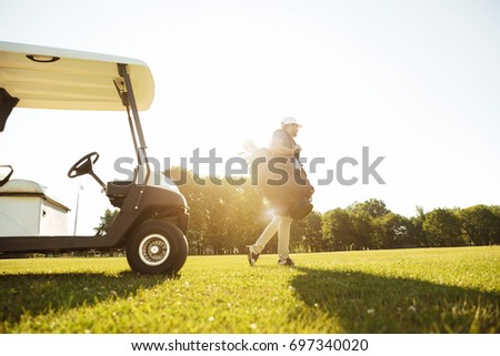 Male golfer walking with golf bag along green course #697340020