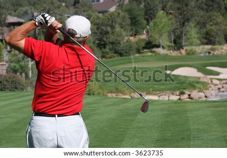 Male golfer with red shirt successfully hitting ball on green with ball and flag visible, focus on golfer