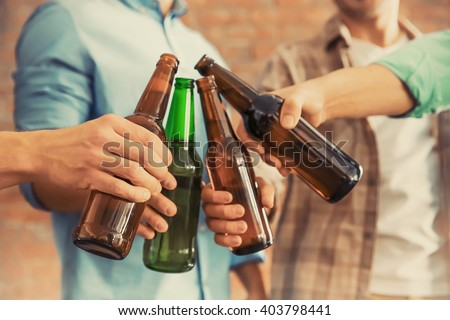 Male group clinking glass bottles of beer on brick wall background #403798441