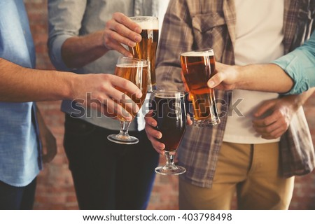 Male group clinking glasses of dark and light beer on brick wall background #403798498