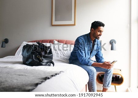 Male guest in boutique hotel sitting on edge of bed checking emails and social media on mobile phone in the morning Сток-фото ©