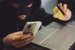 Male hacker in a robber mask uses phone, credit card and laptop in some fraudulent scheme. Cyber thief stole the personal data and credit card information. Hacker uses malware to steal user's money.