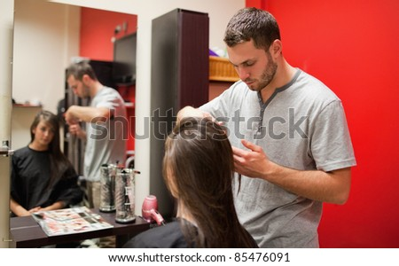 Male hairdresser cutting hair with scissors