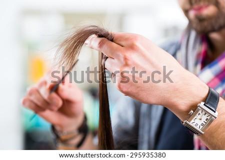 Male hairdresser cutting woman hair in hairdresser shop