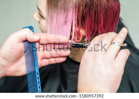 Male hairdresser is cuting pink hair of woman close up.