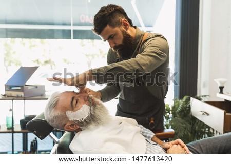 Male hairdresser preparing for shaving senior client