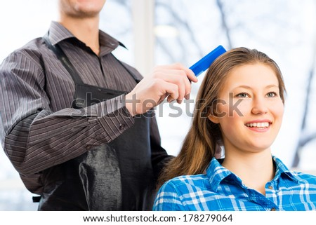 male hairdresser puts woman\'s hair in a hairdressing salon
