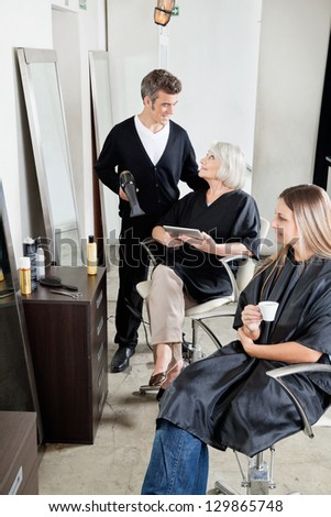 Male hairdresser with female client's in beauty salon