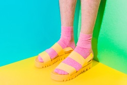 Male hairy legs in socks staying in women's sandals on bold background in the corner with strong shadows. Minimal pride concept. Body part