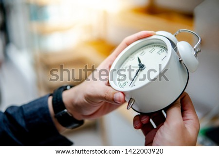 Male hand adjusting or changing the time on white clock. Time management concept.
