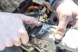 male hand adjusts the gear in the chainsaw, close-up, selective focus