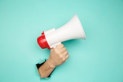 Male hand arm hold megaphone isolated through torn blue background