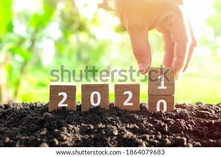 Male hand bury year 2020 to change to 2021 in wooden blocks cubes. New year, hello and goodbye concept.