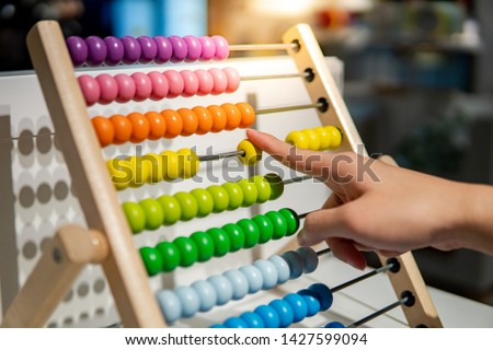 Male hand calculating with beads on wooden rainbow abacus for number calculation. Mathematics learning concept