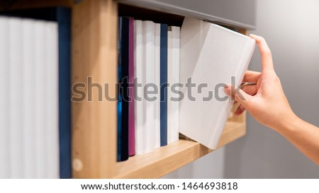 Male hand choosing and picking white book on wooden bookshelf in public library. Education research and self learning in university life concepts