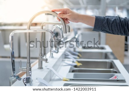 Male hand choosing stainless steel water tap in furniture store. Home improvement for domestic kitchen.
