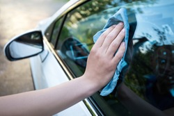 male hand cleaning car window with blue microfiber cloth