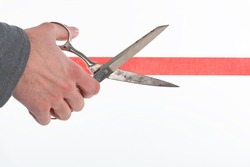 Male hand cutting through red tape with scissors isolated on white with a shallow depth of field and copy space