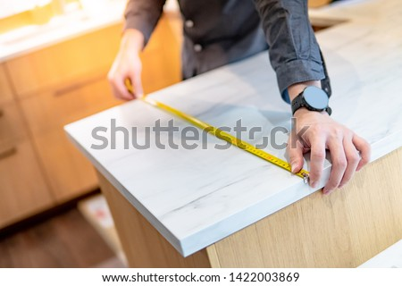 Male hand designer using tape measure for measuring white granite countertops on modern kitchen counter in showroom. Shopping furniture material for home improvement. Interior design concept