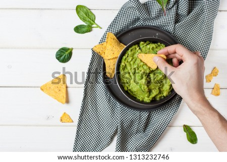 Male hand dipping nachos in guacamole sauce #1313232746