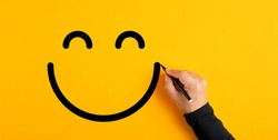 Male hand drawing a smiling happy face sketch on yellow background. Client satisfaction, service or product evaluation concept.